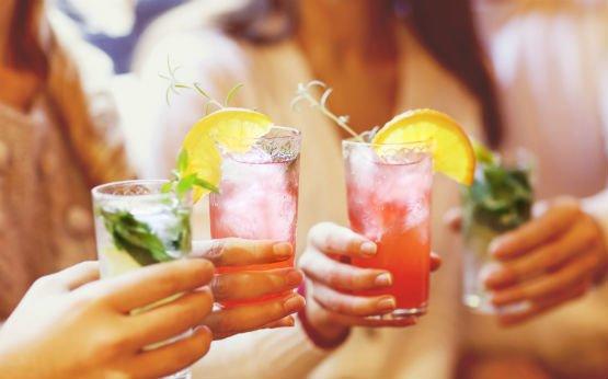 mulheres a fazerem brinde com cocktails alcoólicos