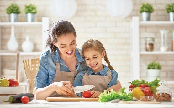 mae e filha a preparem legumes
