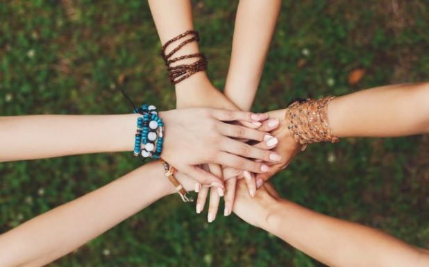 mãos de amigas umas em cima das outras com pulseiras da amizade